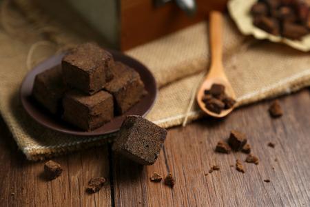 los pedazos del azúcar de Brown en cajas de madera y placas