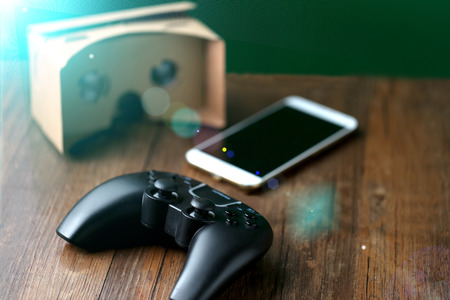 Virtual reality glasses on the table, games consoles and smart phones Stock Photo