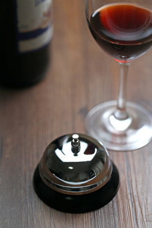 service bell: Service bell and red wine on the table