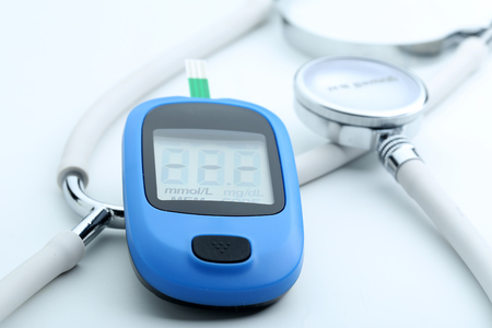 self testing: Blood glucose meter and stethoscope on white background