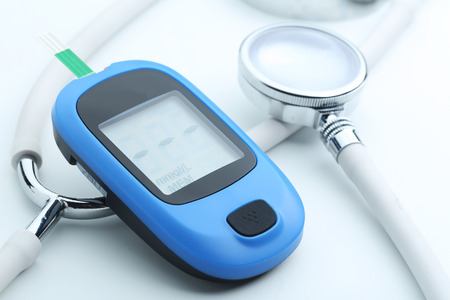 Blood glucose meter and stethoscope on white background