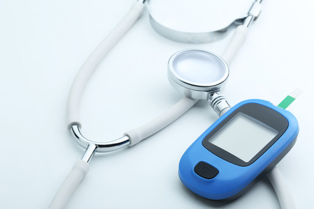 Blood glucose meter and stethoscope on white background Stock Photo - 65616007