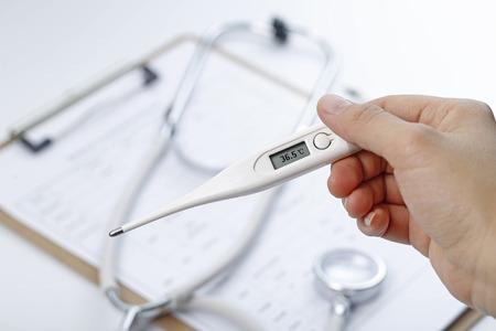 body temperature: hand holding a theromenter mesuring body temperature