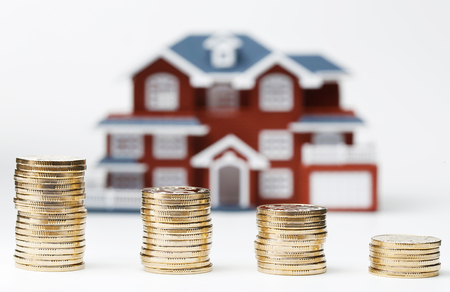 house prices: RMB coins stacked in front of the housing model (house prices, house buying, real estate, mortgage concept)