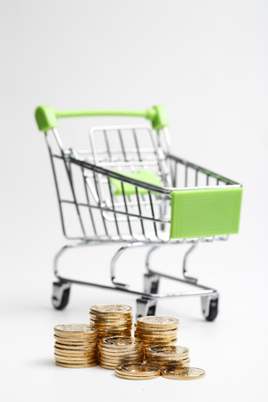 common people: COINS pile and shopping cart on a white background Stock Photo