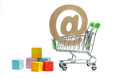 wooden symbol of at sign in shopping cart, Online shopping concept Stock Photo