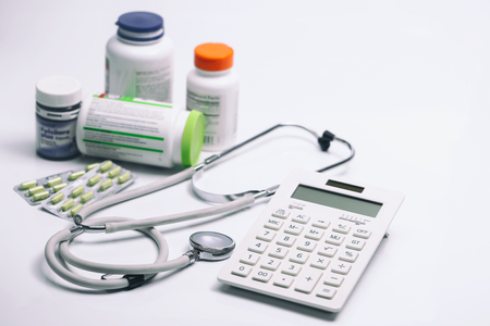 healthcare costs: calculator, stethoscope and medicine bottles on white background
