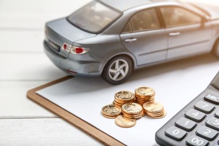 Modèle de voiture, calculatrice et pièces de monnaie sur table blanche Banque d'images - 80081922