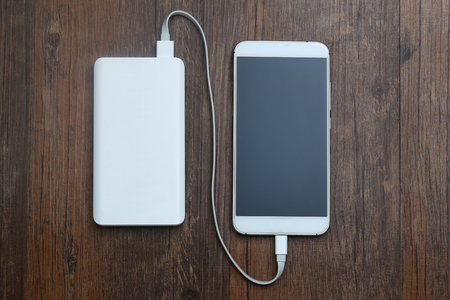powerbank and cellphone on wooden table 스톡 콘텐츠