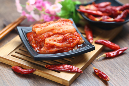 Korean kimchi in black plate on bamboo