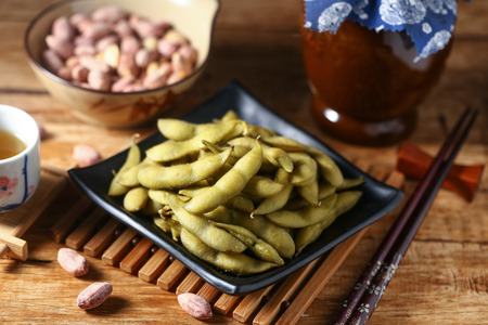 close up food: boiled edamame in black plate with rice wine and peanut