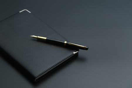 golden pen,notebook,calculator and glasses on black desk