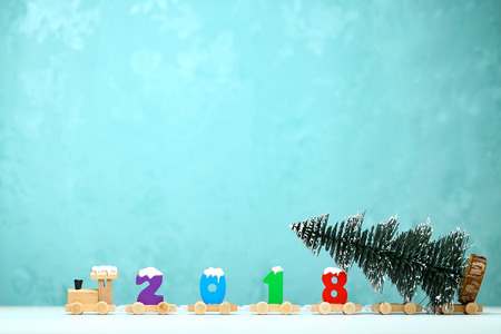 2018 happy new year,wooden toy train carrying numbers and Cristmas tree,covering snow