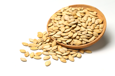 pumpkin seeds in wooden plate isolated on white background 写真素材