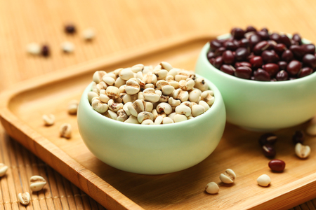 red beans and coix seeds in green bowl on bamboo