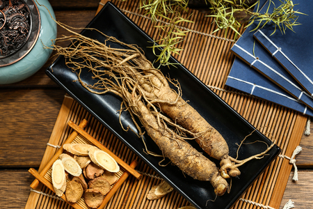ginseng in black plate on wooden table Stock Photo