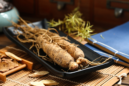 ginseng in black plate on wooden table