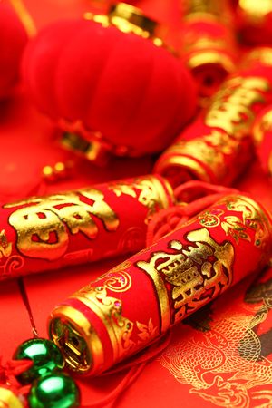 Chinese new year lanterns and fake firecrackers on red background that says good luck and happiness