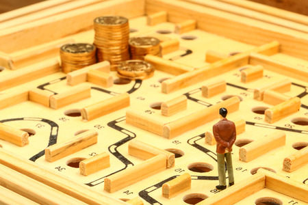 business man standing on wooden maze looking at a pile of coins faraway