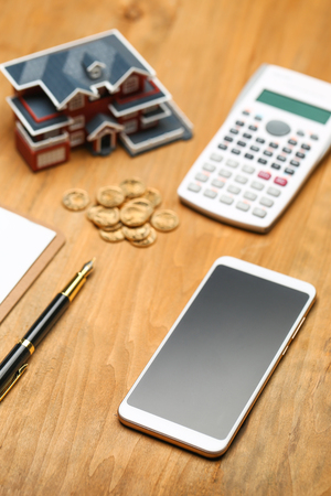 house model,calculator,pen,and coins on wooden table  Stock Photo