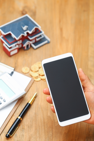 hand holding a smartphone in front of house model,calculator,pen,and coins on wooden table