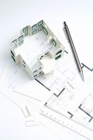 Modelo de casa, plano, lápiz y regla sobre fondo blanco.