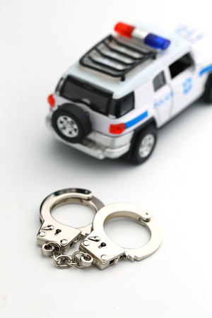 toy police car and handcuffs model isolated on white background