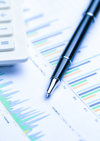 pen,glasses and calculator on Financial stock market graphs analysis chart