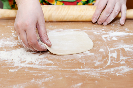 high calorie foods: Female hand holding a circle of dough kitchen table. Stock Photo