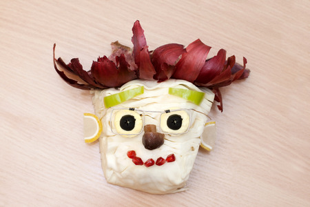 onion peel: Face from cabbage eyes olives nose mushroom hair onion peel wooden background.