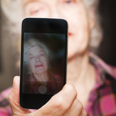 80s adult: Portrait  of senior woman taking photo youself with using mobile phone