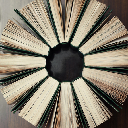 books on a wooden surface: Books stand around on a wooden surface. View from top.