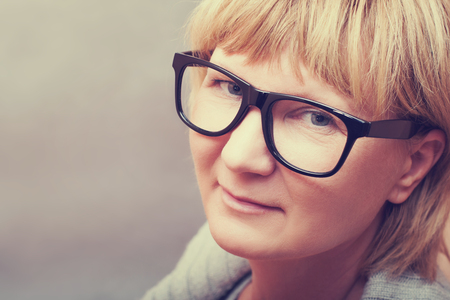 average age: Adult woman in glasses look at camera gray background point shot from top Stock Photo