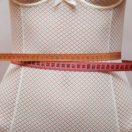 without clothes: Two sewing centimeters on the womans waist, close-up. Stock Photo