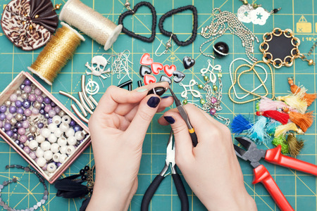costume jewelry: Woman making costume jewelry, earrings. Home made. Tools. Top view. Work place.