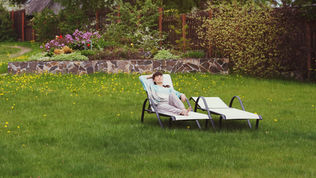recliner: Girl has rest on a recliner in the yard. Copy spase.