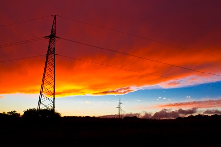 Armageddon sunset - red burning sky and long transmission power lines - lattice tower photo