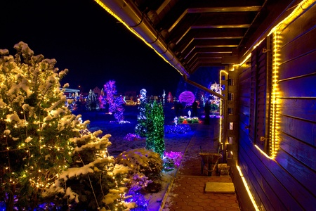 Christmas fantasy - trees and wooden house in lights on a beautiful winter evening