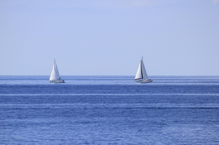Two sailboats on open blue sea horizon
