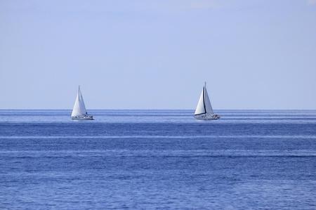 Two sailboats on open blue sea horizon