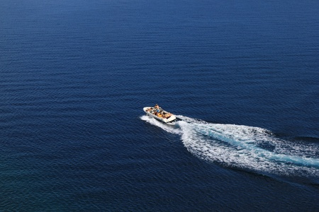 Speed boat aerial view on blue open sea water photo