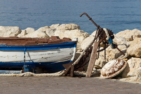 Old wooden boat, rusty anchor, chain and ropes