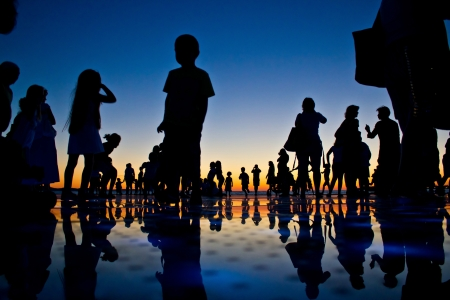 People reflections on colorful sunset in Zadar, Croatia