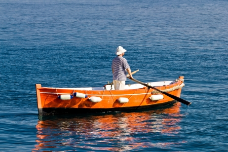 Sailor rowing on wooden taxi boat in Zadar, Croatia photo