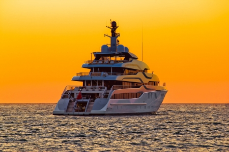 Luxury yacht on open sea at golden sunset