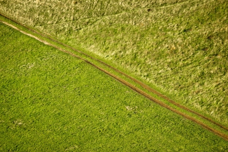 Green meadow diagonal tractor track aerial view photo