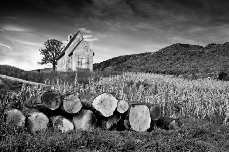 kalnik: Stone mountain church and pile of chopped trees in black & white, Kalnik, Croatia