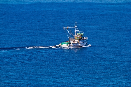 Fishing trawler on open blue water aerial view