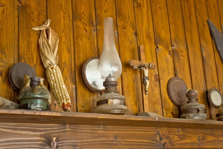 Old lantern, crucifixion, corncob and paraffin lamp on shelf, with wooden background photo