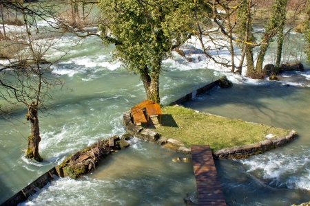 Resting place in pure nature on small river island in village Rastoke in Croatia photo